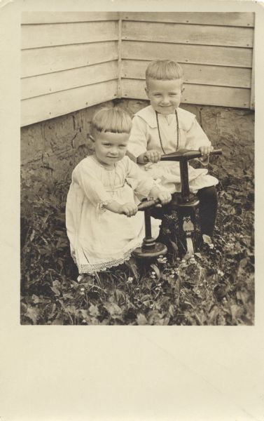 Two children pose outdoors in the corner of a yard next to a building. They are sitting on tricycles or pushbikes, one has an owl logo on the front. Both are wearing light colored clothing and have identical haircuts. Foliage and flowers are at their feet.