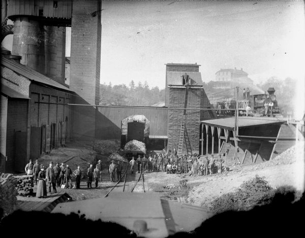 Elevated view of York Iron works. Large group of men posing in yard. The boardinghouse is on a hill in the far background. Early iron was mined at Mayville and Iron Ridge in Dodge County. Early foundries did business in castings, agricultural machinery and blacksmithing.