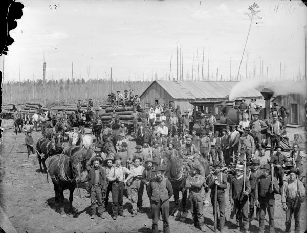 Elevated view of lumber camp with loggers posing in front of a train loaded with logs.