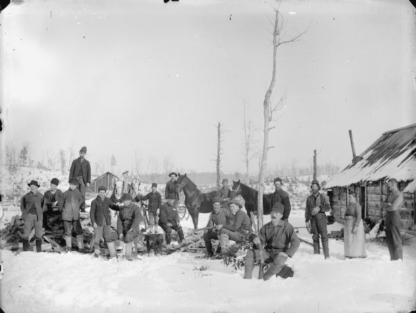 Group of men, a dog and one woman posed standing and sitting in the snow-covered yard near a wooden building,. Three men hold rifles, two men display horses, while another displays a team of two horses.