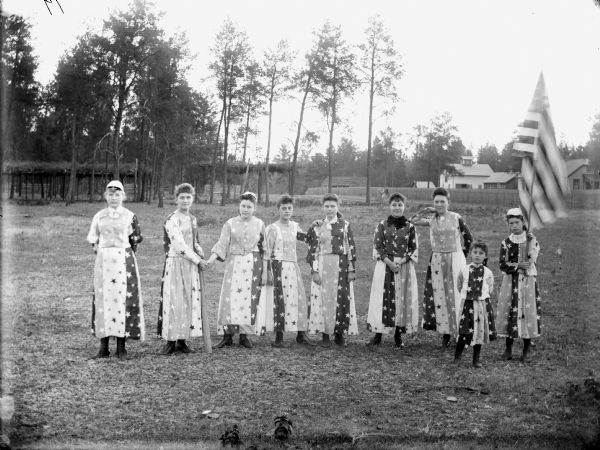 "Nine girls are posing standing and wearing patriotic costumes. One girl is holding a flag of the United States. Probably a smaller group, from a total of twenty-eight girls, dressed in red, white and blue costumes, drilled by J.R. Ogden for a Memorial Day honor guard in 1904. Based on information in the ""Melrose Chronicle,"" May 23, 1984, citing an article of April 28, 1904."