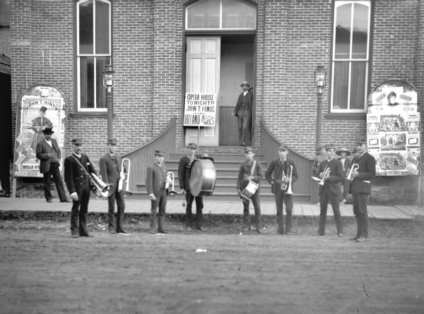 "Brass band with eight musicians posed standing on the street in front of the Opera House. At the far right is Carl Pope. Signs advertise ""John T. Hinds in Ireland As Tt Was."" Two men stand in the open doorway of the Opera House entrance, and two boys stand on the sidewalk."