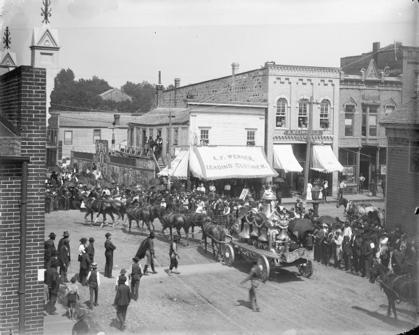 Elevated view of a crowd gathered at the intersection of First and Main Streets to watch a bell wagon pass in a circus parade, probably the Ringling Brothers Circus. The bell wagon has been owned by the Circus World Museum since 1985.