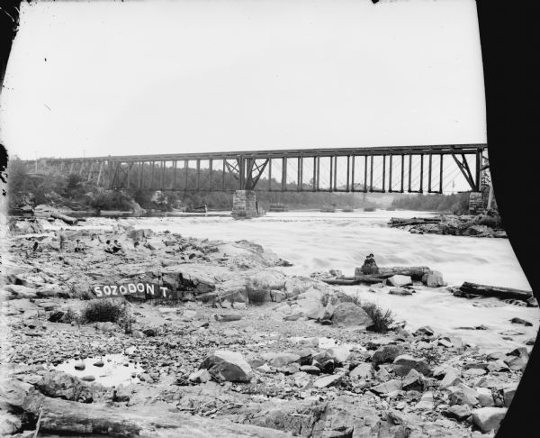 "View from shoreline of two women posed on logs on rocky shoreline by the river. Four or five young boys sit on the rocks on the left. There is a railroad bridge is in the background. Graffiti letters painted on a rock nearby say, ""Sozodon T."" There are wooden structures in the river beyond the bridge, perhaps sorting piers for log transportation."