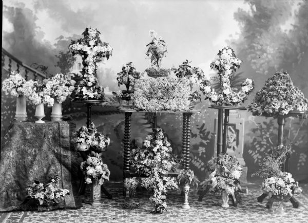 Studio portrait of various bouquet wreaths in several shapes, including a cross and anchor, in front of a painted backdrop.