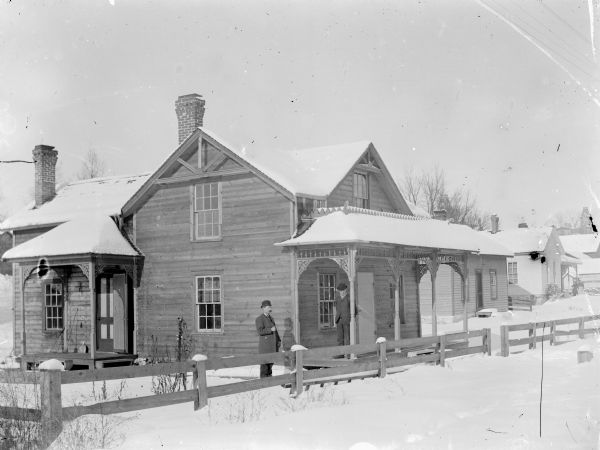 View from road of two men standing behind a fence next to a snow-covered frame house. A woman and young girl pose standing on the porch of a house two houses down on the right.