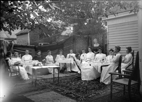 Group of fifteen women gathered around three tables behind a home, probably the DMC Club, an exclusive social and sewing society named for an imported brand of French fancywork cotton crocheting, also known locally as the Damn Mean Crowd Club by outsiders. Identified by Joanne Dougherty, sitting from left to right, as: unidentified, Mrs. Ludovic Dimmick, Mrs. Louis Jones, unidentified, Mrs. Anton Johnson, Mrs. Rufus Jones, Mrs. J.J. McGilivray, Flora LeClair (in rocking chair), unidentified, Mrs. John Marsh, unidentified, Edna Richards Turner, Mrs. Will Richards, Nina Mason Werner, and Mrs. Charles Van Schaick, standing. Behind them quilts are hanging on a line from the edge of the house all the way across the background, and there are rugs on the ground.