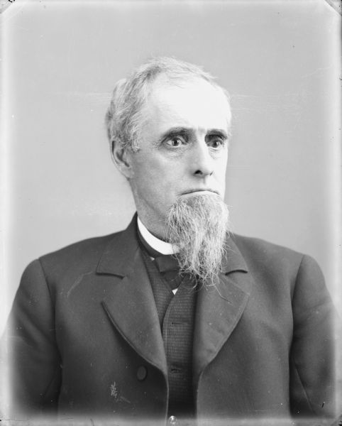 Quarter-length studio portrait of man in clerical collar, facing slightly to right, with deep set eyes and long goatee.