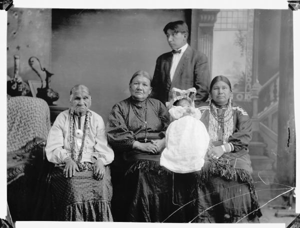 Five generation studio portrait of a Ho-Chunk family. Sitting (l to r) Great-Great-Grandmother, Nancy Brown; Great-Grandmother, Lucy Goodvillage, Blowsnake; Grandmother, Annie Blowsnake, Thundercloud. Standing: Adam Thundercloud; Baby: son of Adam Thundercloud. In the background is a painted backdrop.