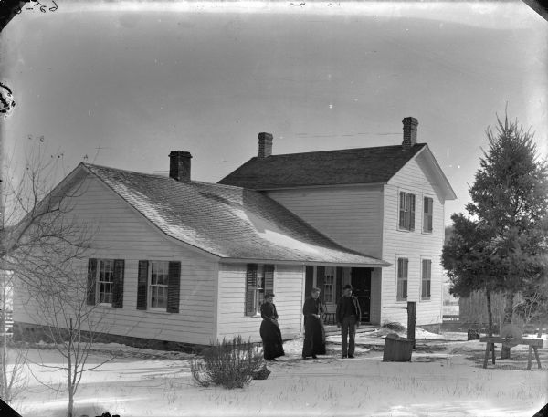Two women and a man are posing standing on the snow-covered ground in front of a frame house. There is a hand-operated knife grinder in the yard.