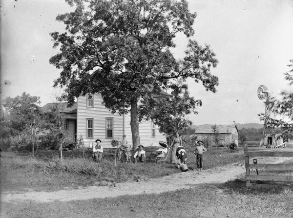 Two men and a child are posing sitting, with a woman, girl, and boy standing near a baby in a baby carriage. There is a cow drinking from a bucket. The group is in front of a two-story frame house, farm buildings, and a windmill.