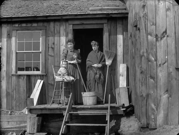 Two women are standing on the small porch outside an open kitchen door, near implements used for daily household tasks such as washing, scrubbing, sweeping, and child care. A young child is sitting in a high chair on the porch near a wooden bucket.