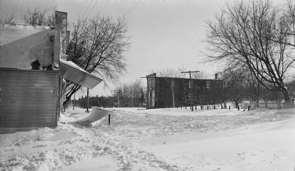 Winter scene looking east on Main Street (Highway 42), with wooden commercial buildings on both sides of the street. The building on the left, 4168 Main Street, has a large wooden awning and a snow drift in front. It housed general stores under the Lundberg, Vorous, Krause and Alwes names. The building in the background, now 4153 Main Street, housed the Levi Vorous store in front and Noble's blacksmith shop in the rear.