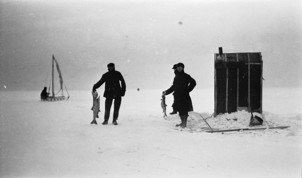 Two men holding large fish pose near an ice fishing shanty off of Fish Creek. Another man stands behind them. There is man on an iceboat in the left background.