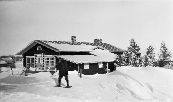 Ferdinand Hotz poses wearing snowshoes at his cottage in Fish Creek, now 4108 Main Street. There is a large snowdrift in the foreground.