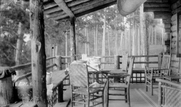 The porch of the Hotz cottage at Europe Lake, furnished with a rustic table, chairs and benches; the table has been set for a meal. The cottage and porch are of log construction.