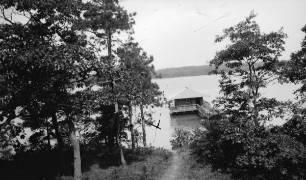 A walkway with rustic railing leads to the Hotz family boathouse on Europe Lake. A well-worn path leads downhill to the water.
