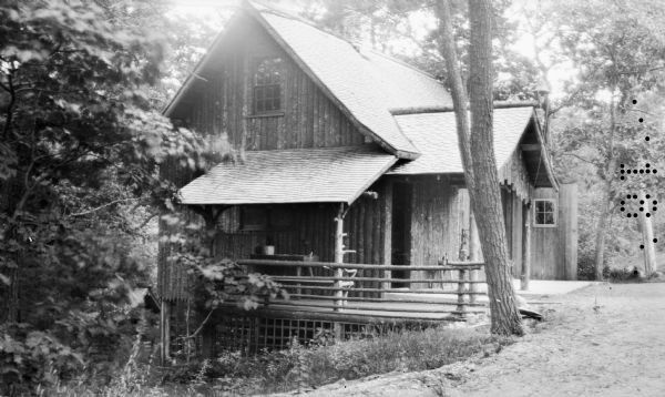 A vertical log-sided garage with lean-to porch stands on the side of a hill in the woods. There is a rustic table on the porch.  This building was located across the drive from the Hotz cottage.