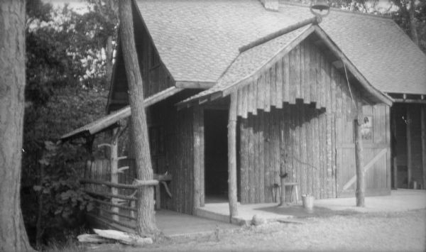 The garage, with vertical log siding, near the Hotz family cottage at Europe Lake. There is a pump on the front porch, and a bell with a rope on the peak of the roof. There is a lean-to porch on the side.