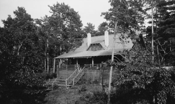 The lake side of the Hotz cottage on Europe Lake, showing the porch with rustic lattice work, and steps. A central dormer is flanked by chimneys.