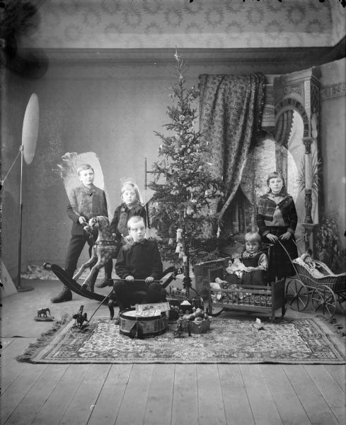 Studio portrait of Gerhard Gesell's five children (l to r: Arnold, Bertha, Robert, Gerhard, and Wilma) posed around a Christmas tree with their gifts.