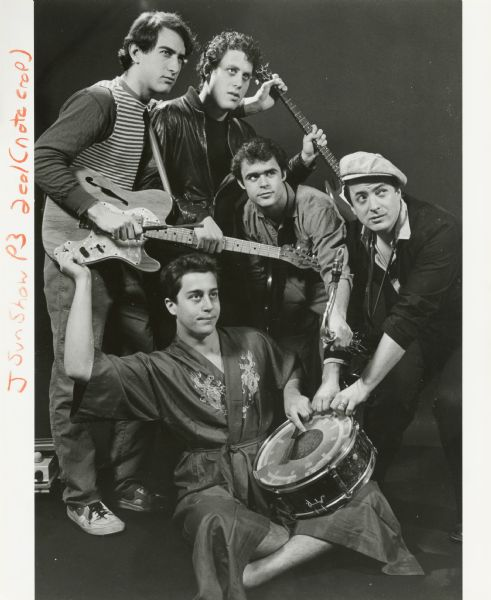Publicity photograph of the five band members of Swamp Thing, a Madison, Wisconsin rock group. Clockwise from top are Jonathan Zarov, Bob Appel, Mike Kashou, David Miller, and Steve Bear (seated). They are holding two electric guitars, a saxophone, and snare drum. Steve is wearing a silk bathrobe with an embroidered dragon design.