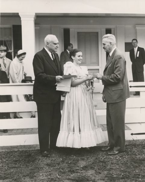 Ruth DeYoung Kohler II, presents the key to Wade House to Dr. William McKern, of the Wisconsin State Historical Society. The century-old stagecoach inn and adjoining buildings were purchased by the Kohler Foundation, Inc., in 1950, and restored under the direction of the young lady's mother, the late Mrs. Herbert V. Kohler. Her father, Herbert V. Kohler, chairman of the Kohler Foundation, is standing on the left. Other people can be seen standing behind the white fence and on the porch.