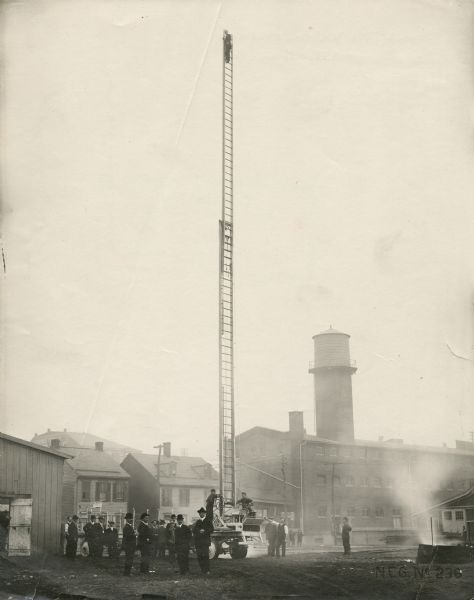 Fire fighting scene in which a man is at the top of a very tall ladder mounted on a hook and ladder fire truck. A group of men observe. A haze of smoke fills the air. Factory buildings and two houses appear in the background.