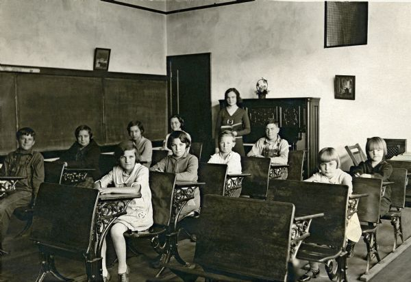 Ten students sitting at their desks in the classroom at Bay Hill School. Their teacher, Alice Holloway, stands at the back holding a book. Blackboards cover the wall on the left. A door and a piano are along the back wall, on which hang two framed images.
