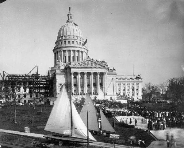 "Elevated view of the Wisconsin State Capitol building, showing steel work of North Wing under construction. Crowds of people are gathered on the lawn for the Fall Festival. More people are gathered on the roof of the Capitol building just below the dome.  Two boats are on display in the foreground near a sign that reads: ""Mendota Yacht Club 'Boost Madison Lakes.'"" The iceboat on the right is the Princess II and the sailboat on the left is the Neireid."