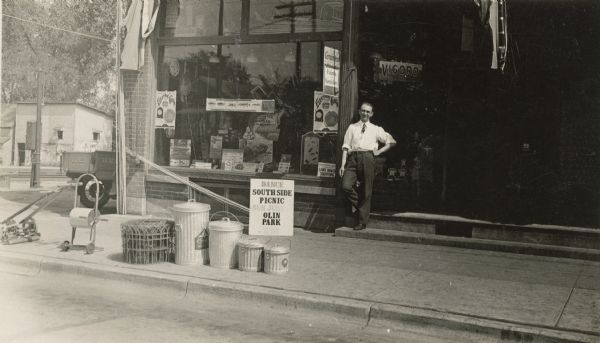 "Henry Esser stands on the step in front of Koltes & Esser Hardware in the 300 block of West Lakeside Street. Fencing, garbage cans, a hose reel and lawn mower are on display at the curb. The rear of the company truck can be seen parked on the left. The window is full of merchandise and signs. Bamboo fishing poles are stacked diagonally across the front. A sign for the South Side Picnic to be held on Sunday, June 14th, 1931, is propped against the store foundation. It reads ""Dance, South Side Picnic, Sun. June 14, Olin Park, Board Compliments, Capital City Lumber Company."" Many of the South Madison businesses displayed similar signs."