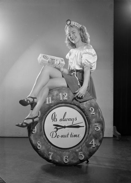 "Donut queen posed for advertising campaign. The female model is holding a box of donuts and is sitting on a large clock bearing the slogan: ""It's Always Do-nut Time."""