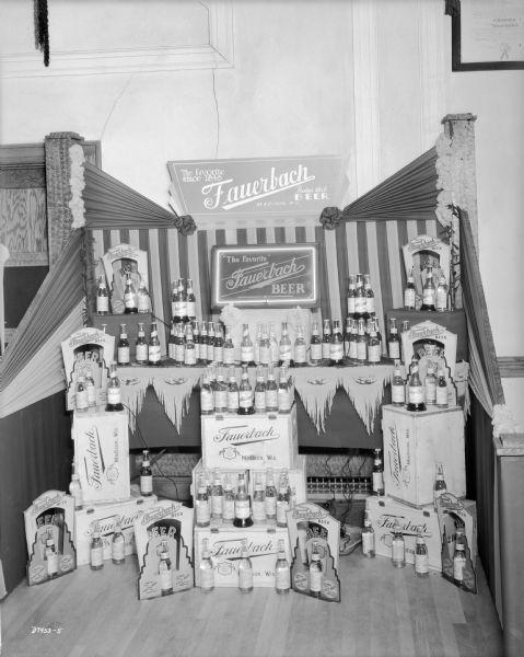 The Fauerbach Beer display at the Grocery Convention. The display consists of many bottles of beer, beer cases, die cut cardboard displays, cloth bunting and two signs. One sign in the center has a neon border.