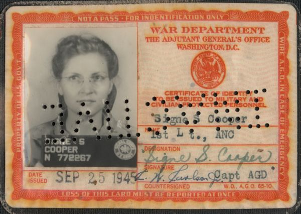 "The identification card of Signe S. (Skott) Cooper, 1st Lt., ANC. (First Lieutenant, Army Nurse Corps.) The card was issued SEP 25 1945. Her photograph is on the left, name and signatures on the right. When the card is reversed, the punched holes across the ID spell ""INACTIVE."""