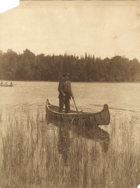 View across water of a Menominee man standing in a canoe in a marsh. He is holding a paddle in his hand. Behind him on the left is another canoe with three people. The far shoreline is lined with trees.