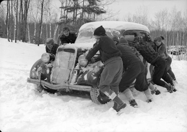 Scouts at a winter camp push a car stuck in deep snow. Trees are in the background.