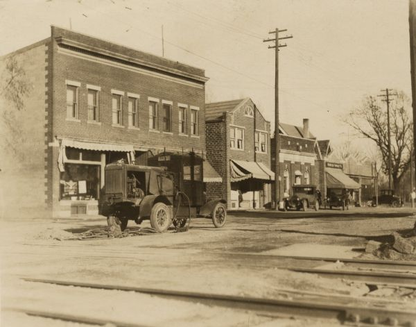 "View across street looking west towards the north side of West Lakeside Street. Three known businesses are the South Side State Bank (3rd from the left), Universal Grocery Company (4th from the left) and Bontly's Arcade (5th from the left). The awning on the building on the left says ""Hardware & Paint."" A man is standing in the doorway of the building next to it. Two automobiles are parked at the curb. An Ingersoll-Rand truck with a compressor and jackhammers sits in the middle of the street. Railroad tracks are in the foreground."