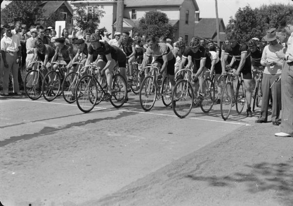 View from left front of male bicycle racers at the start of a race. Some of the men wear hats, and two wear helmets. On the far right a man smoking a cigarette holds the starting pistol, and next to him another man smoking a cigar is looking down at a stopwatch in his hand. On the opposite side of the street is a crowd of spectators standing in front of houses.
