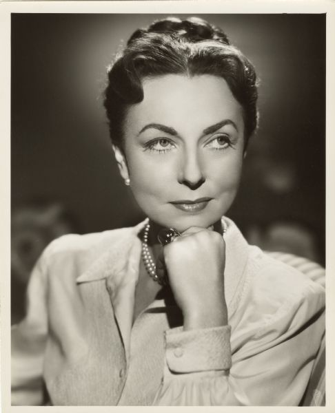 Publicity photograph of actress Agnes Moorehead. She is resting her chin on her hand and is looking off to the side with a slight smile. She is wearing a pearl necklace and earrings, and a large cabochon ring on her left ring finger.