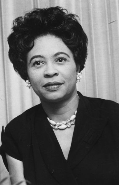 Portrait of Daisy Bates wearing a dark dress and beaded earrings and necklace.