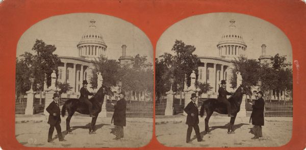 "Stereograph. This view from East Washington Avenue shows photographer Andrew Dahl on his horse ""Curnel"" in front of the Wisconsin State Capitol. Dahl had just returned from the Centennial Exposition in Philadelphia. Two other men stand near the horse."