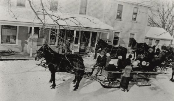 Elevated view of a group of people posing on and around horse-drawn sleds. There is a man on the porch of the building in the background.