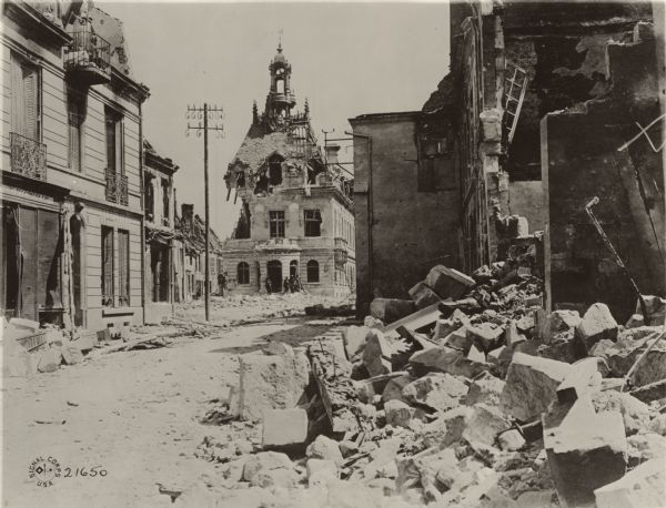 Street in Fismes, France destroyed during the Battle of Fismes. The badly damaged town hall can be seen near the center, with rubble from other buildings in the foreground.