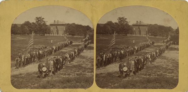 Outdoor elevated view of a reunion of the Norwegian American men of the 15th Regiment of the Wisconsin Volunteer Infantry at Luther College. They are posing in two lines holding the American flag and the Norwegian flag.
