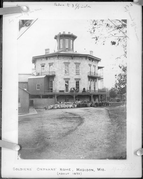 "Group of people posing outside of Soldiers' Orphans Home, located on Spaight Street between Paterson and Brearly Streets. The building was originally constructed by Governor L.J. Farwell, about 1853, as a private residence. It was opened on January 1st, 1866 as the orphan asylum; Mrs. Cordelia Harvey, widow of Governor L.P. Harvey, was in charge. According to <i>The Jefferson Banner</i>, 23 January 1867, this photograph was sold for $3.75, with ""35% of the proceeds to go for the benefit of the home . . . Every person should purchase a copy and thereby assist the soldiers' orphans of Wisconsin in obtaining an education."""
