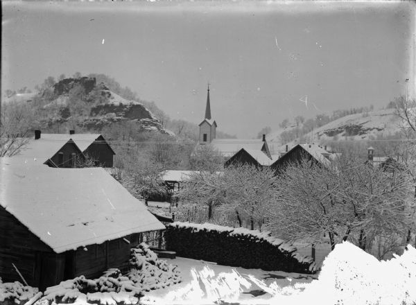Winter scene overlooking town, showing Baptist church in background.
