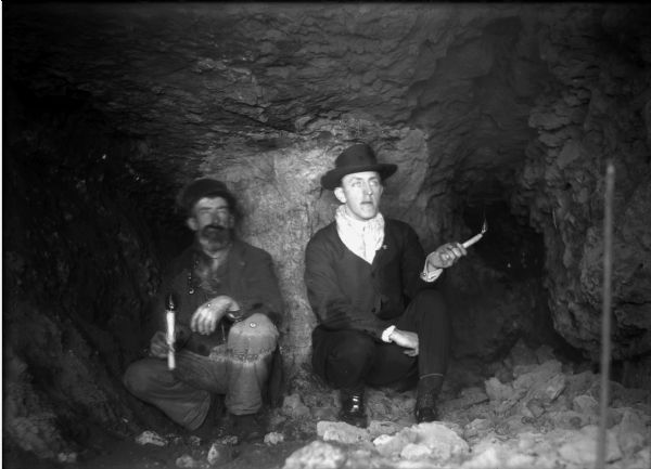 Interior of a lead mine showing two miners kneeling with candles in their hands.