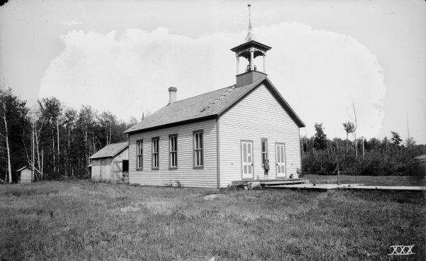 Exterior view of the district school house property, with a young boy standing on the front steps. There is a hand-pump on a wood platform in front of the building.