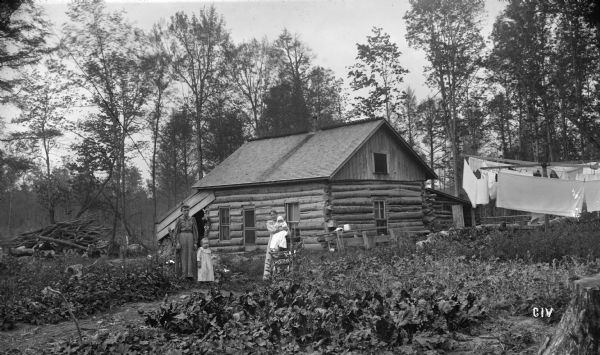 Log cabin of N.G. Willard on 80 acres of land. Two women, a young child, and an infant are posing outdoors in the yard. Laundry is hanging on lines on the right. Trees surround the log house.