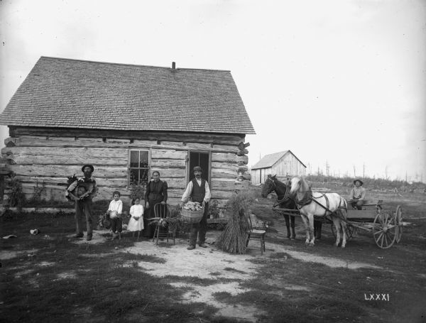 The family of French-Canadian immigrant Peter Lagacy, posing with produce, including a large cabbage, potatoes, and carrots, in front of their log farm home.